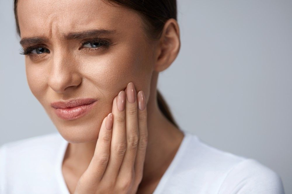 woman with cavity holding her face