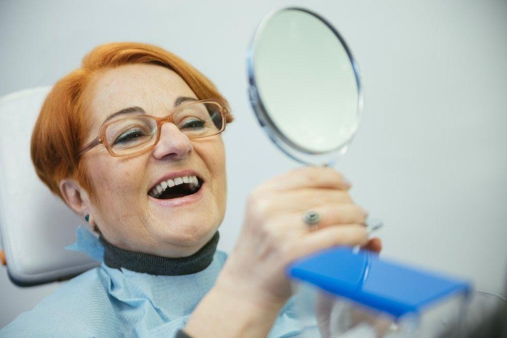 dental bridges patient examining teeth