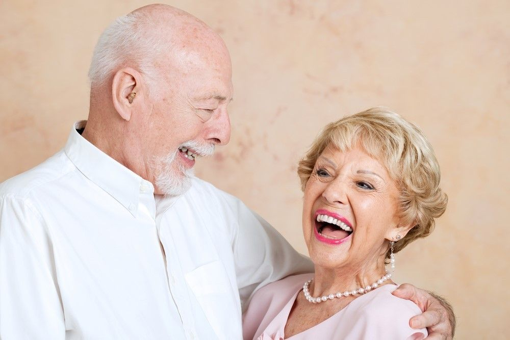 happy couple showing their dentures